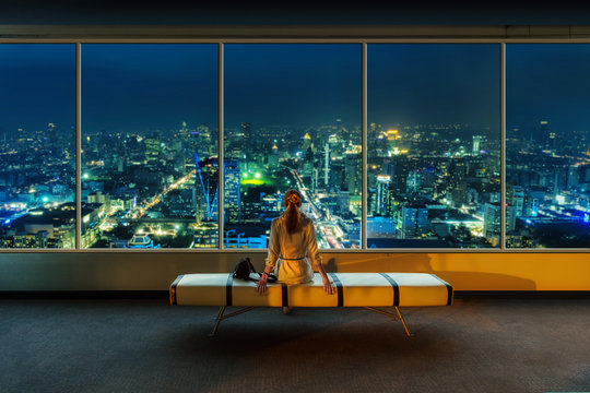 Woman look out the window at night cityscape