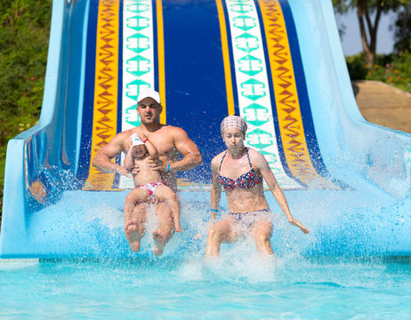 Happy family at waterslide outdoors