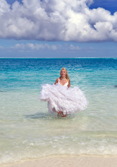 young beautiful woman in a dress of bride runs on waves of sea..