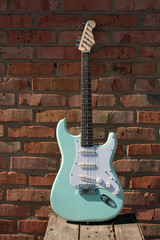 electric guitar on a brick wall