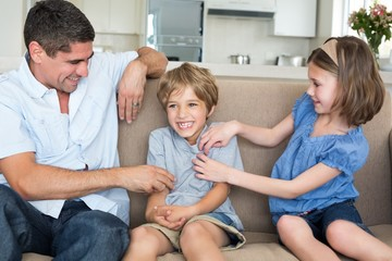 Father and daughter tickling boy on sofa