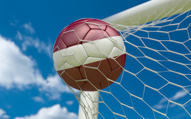 Flag of Latvia and soccer ball in goal net