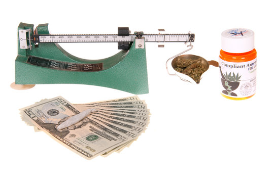 Scale for weighing marijuana with container, roll up joint and money for the transaction