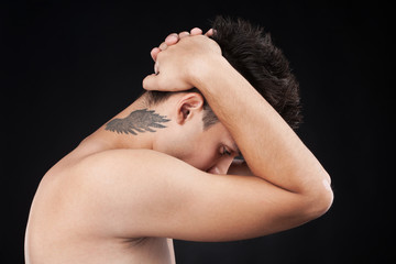 nude young man with tattoo on neck.