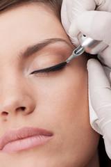 professional tattooist making permanent make-up.