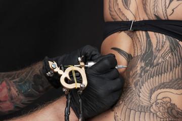 professional tattooist making picture on skin.
