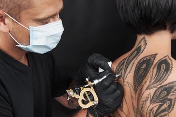 professional tattooist making back tattoo.