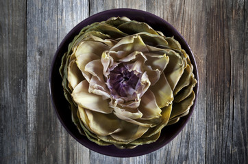 artichoke like lotus flower on bowl on wooden table