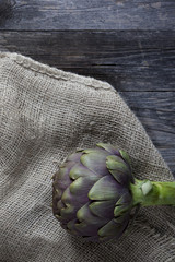 one artichoke on jute sack on wooden rustic table