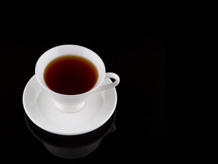 A cup of tea over black background
