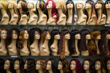 rows of mannequins ina wig shop