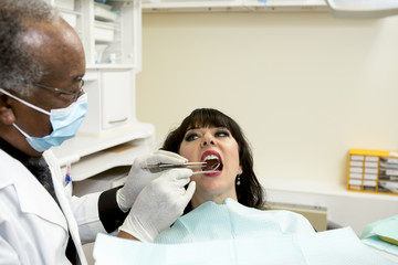 Dentist checking for cavities during oral exam