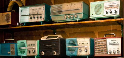 vintage radio on a wooden shelf (toned image )