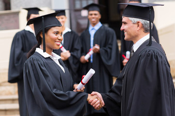 afro american female graduate handshaking with dean