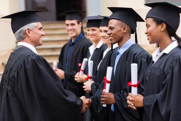 professor handshaking with graduates