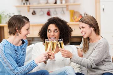 drei freundinnen stoßen mit sekt an