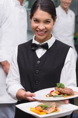 Happy waitress holding steak dinner and salmon dinner
