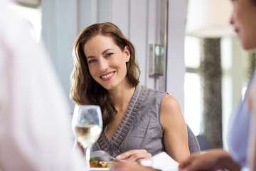 Smiling woman having wine with friend at restaurant