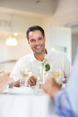 Smiling man having wine with friend at restaurant