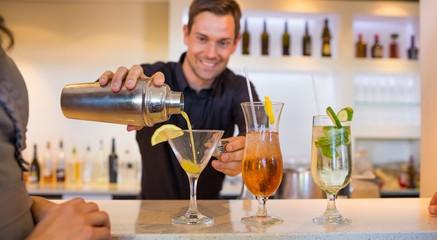 Smiling bartender preparing a drink at bar counter