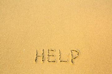 Help, written in sand on beach texture.