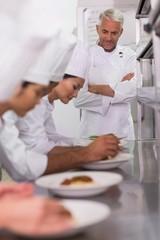 Head chef watching row of chefs garnishing spaghetti dishes