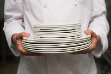 Chef holding stack of plates