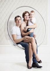 Young family with baby boy while sitting in swinging chair