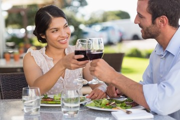 Happy couple on a date toasting with red wine