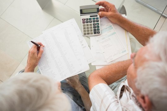 Senior couple using the calculator to pay bills
