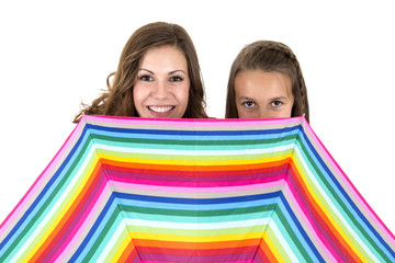 A woman and a girl behind a rainbow colored umbrella