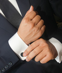 A man in a black suit straightens his cufflinks