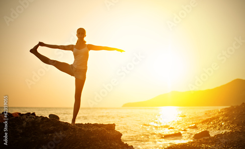 Wall mural woman doing yoga on the beach at sunset