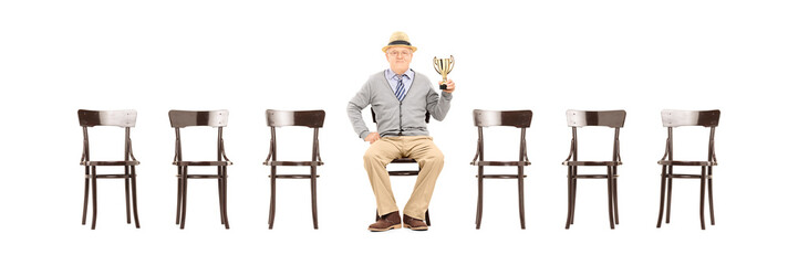 Mature man holding a trophy seated on wooden chair