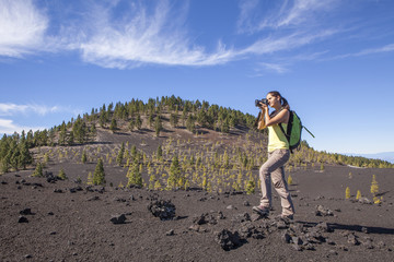 Woman nature Photographer taking pictures outdoors during hiking