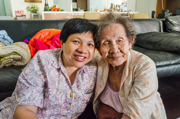 Asian elder mother and daughter hold together in home scenery