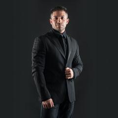 Confident man close up portrait against black background.