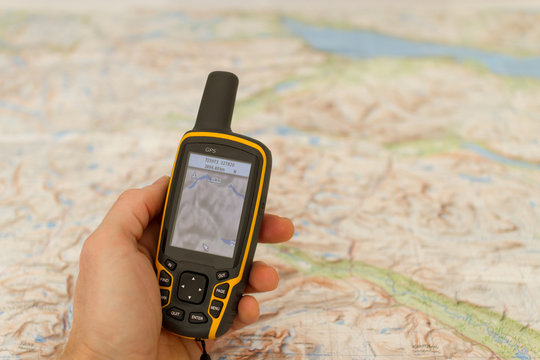 Hand held outdoor GPS and a map.