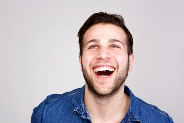 Young man laughing and looking up on isolated gray background