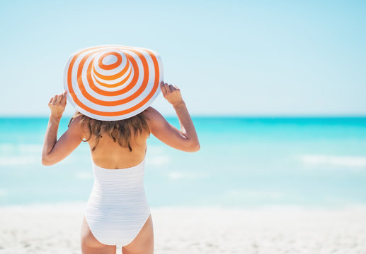 Young woman in hat standing on beach. rear view