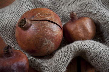 three reds whole pomegranates on rustic sackcloth