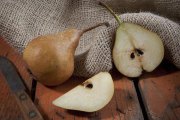 pears on wooden rustic table with knife and vintage sackcloth