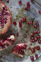 red and juicy pomegranate and grains on ancient silver tray