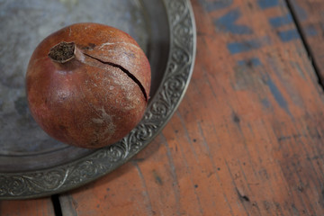 one red pomegranate on silver vintage tray on wooden table