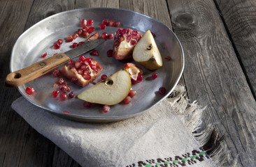 fruits composition pomegranate and pear on tray on wooden table