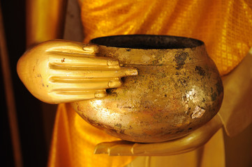 Close up hand of  statue Buddha holding monk  alms-bowl