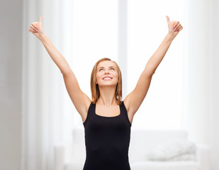 woman in blank black tank top showing thumbs up