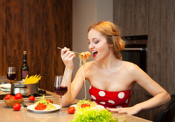 Sexy young blond woman eating spaghetti in the kitchen
