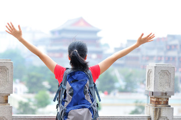 cheering woman tourist open arms at bell tower in xian