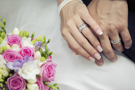 Hands of the groom and the bride with wedding bouquet